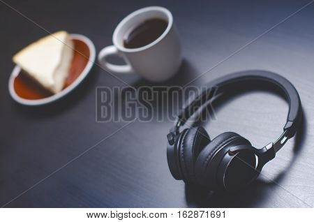 Headphones on a dark background. Music accessories. Bluetooth headphones without cable. Cake and coffee