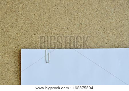 paperclip pin white paper on plywood board