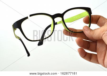 Hand holding broken eyeglasses, mistake in a hand