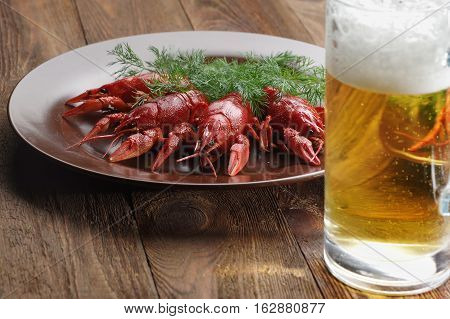 boiled crawfish on wooden surface with a beer and dill. old style plate