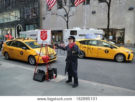 NEW YORK - DECEMBER 15, 2016: Salvation Army soldier performs for collections in midtown Manhattan. This Christian organization is known for its charity work, operating in 126 countries