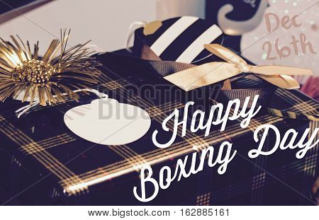 Happy Boxing Day Christmas Gift Wrapping wrapped in black and gold paper with words and Dec 26th and gift tag with room for sale promotion copy or greeting