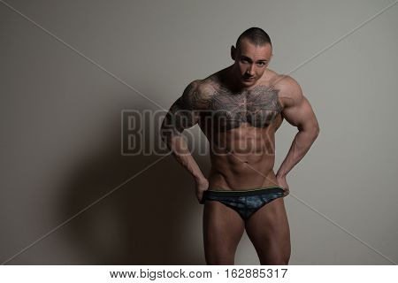 Fitness Man In Pants Isolated On Gray Background