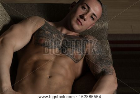 Muscular Shirtless Young Man Laying In Bed