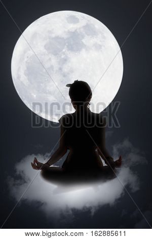 Silhouette of woman doing yoga on the cloud with supper full moon in background blue color tone