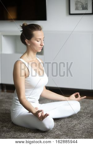 Sporty attractive young woman practicing yoga, sitting in Lotus exercise, Padmasana pose, working out, wearing white sportswear, indoor full length, home interior background