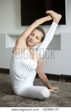Portrait of sporty young woman practicing yoga, sitting in Compass exercise, Surya Yantrasana pose, working out, wearing white sportswear, indoor full length, home interior background