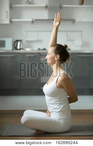 Happy, smiling sporty young woman practicing yoga, sitting in Bound Lotus exercise, Baddha Padmasana pose, working out, wearing white sportswear, indoor full length, home interior background