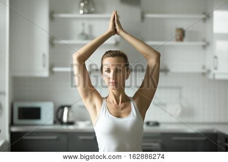 Portrait of attractive woman practicing yoga at home in the morning, standing in yoga pose, working out, doing sun salutation exercises, wearing white sportswear, indoor, home interior background