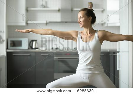 Happy sporty attractive young woman practicing yoga, standing in Warrior Two exercise, Virabhadrasana 2 pose, working out, wearing white sportswear, indoor, home interior background