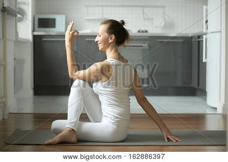 Sporty attractive woman practicing yoga, sitting in Half lord of the fishes exercise, Ardha Matsyendrasana pose, working out, wearing white sportswear, indoor full length, home interior background