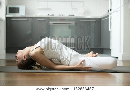 Sporty young attractive woman practicing yoga, lying in Fish exercise, Matsyasana pose, working out, wearing white sportswear, indoor full length, home interior background