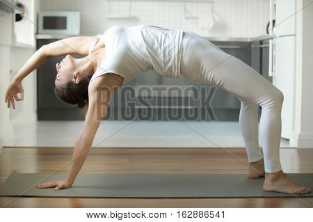 Sporty attractive woman practicing yoga, standing in Bridge exercise, Urdhva Dhanurasana pose, working out, wearing white sportswear, indoor full length, home interior background
