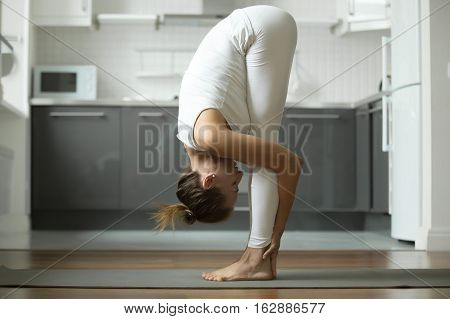 Sporty attractive woman practicing yoga, standing in head to knees exercise, uttanasana pose, working out, wearing white sportswear, indoor full length, home interior background