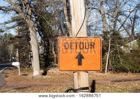 Grunge yellow road sign detour on wooden pillar