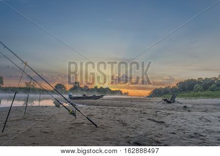 beautiful sunrise over the river against the background of the boat with the motor and fishing-rods for fishing