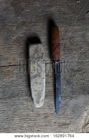 The knife and sharpened on wood background