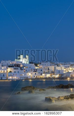 Blue hour of Naoussa village at Paros island in Greece showing the beautiful local church.