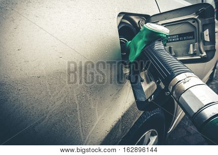 Close up image of modern car refueling on a petrol station. Toned  image with copy space.