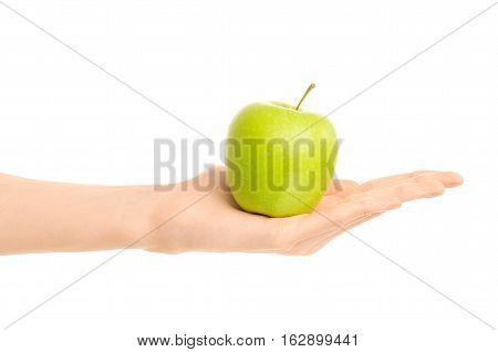 Healthy Eating And Diet Topic: Human Hand Holding A Green Apple Isolated On A White Background In Th