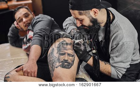 Tattoo master in black gloves, tattoo on the skin of black ink tattoo of his client in the salon.