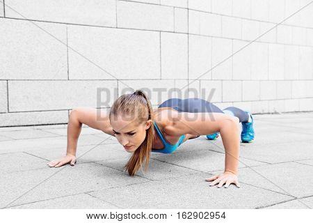 Gorgeous ginger red female warming up and doing some push ups outdoor. Copy space text.