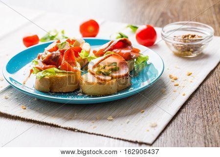 Traditional Italian antipasti bruschetta with salmon and bacon