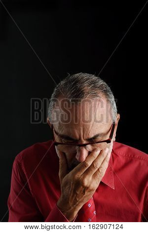 portrait of distressed man with a black background