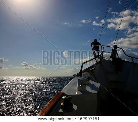 A deep sea fishing boat sailing into the sun off the coast on kenya.