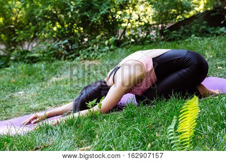 Young attractive girl doing yoga in the park. Healthy lifestyle concept.