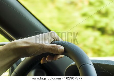 Color Image Of Two Hands Holding A Steering Wheel Inside A Car.