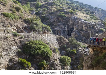 Visitors walking beside the railway line along Caminito del Rey path Malaga Spain
