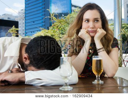 Drunken man sleeps in a bar and caucasian wife is sad