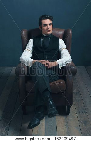 Retro Victorian Dickens Man Sitting On Leather Chair In Living Room.