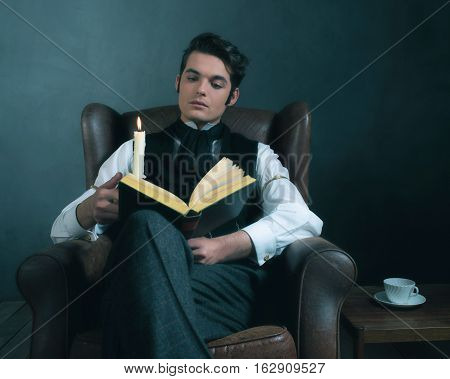 Retro Victorian Dickens Style Man Reading Book By Candlelight.