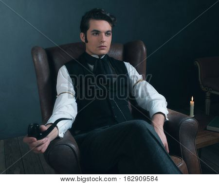 Retro Victorian Man Sitting In Leather Chair Holding Pipe.