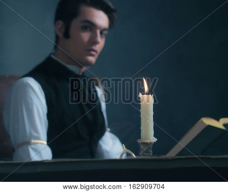 Candlelight By Window With Blurred Retro Victorian Man Reading Book.