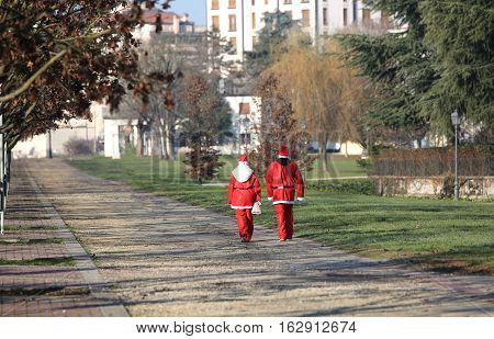 Two Santa Claus Walking On The Public Park At Christmas
