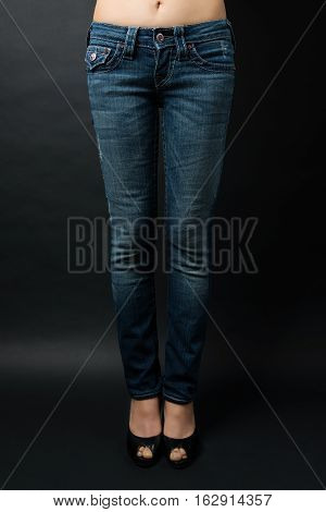 The legs of jeans and boots are beautiful girls. Isolated on black background