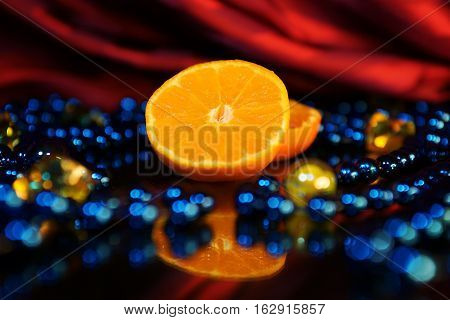 Sliced orange and bijouterie on a black table