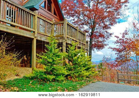 The deck entertainment area of a new log house. Scenic mountains in the distance.