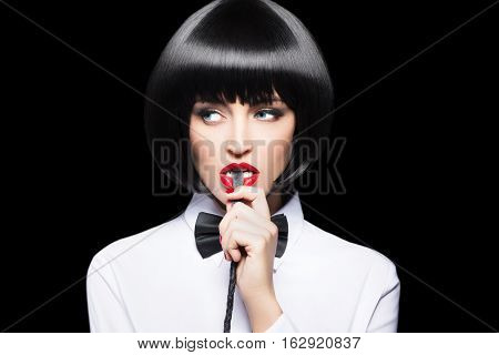 Sexy woman with red lips in wig bite whip portrait bdsm isolated on black