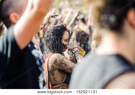 TOLMIN, SLOVENIA - JULY 24TH: HEAVY METAL FAN DRINKING BEER AND ENJOYING THE MUD ON THE METALDAYS FESTIVAL ON JULY 24TH, 2016 IN TOLMIN, SLOVENIA