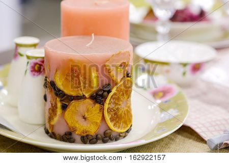 Decorative aroma candle with fruit and coffee on a festive table.