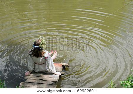 Young Russian girl in national dress linen bathes his feet in the lake, sitting on a wooden bridge