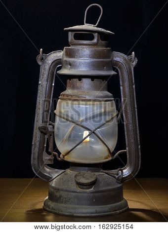 Burning old kerosene lamp stands on the table on a black background