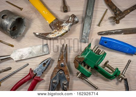 Old tools on wooden background. The metal parts of the tool covered with rust. Composition 4.