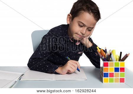 Dissatisfied student about his homework. School boy sitting at his desk.