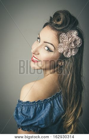 Head and shoulders portrait of smiling fashionable young woman in vintage clothes looking over shoulder studio background