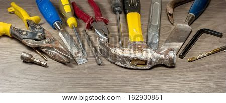 Old tools on wooden background. The metal parts of the tool covered with rust. Composition 7.